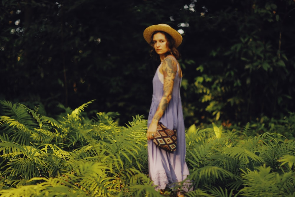woman in blue and white dress wearing brown hat standing near green plants during daytime