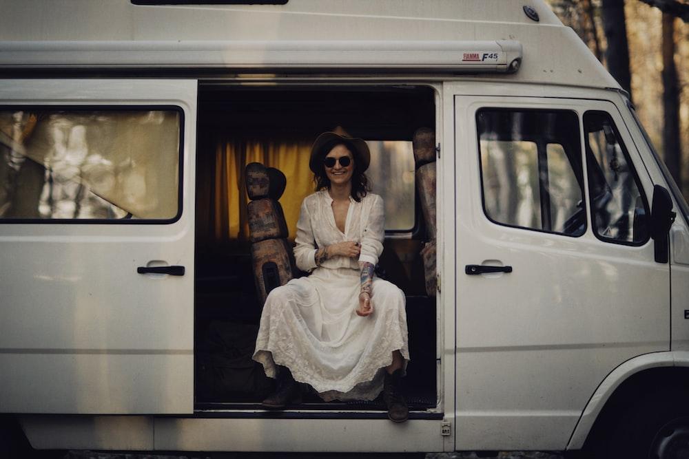 woman in white long sleeve dress sitting on white van