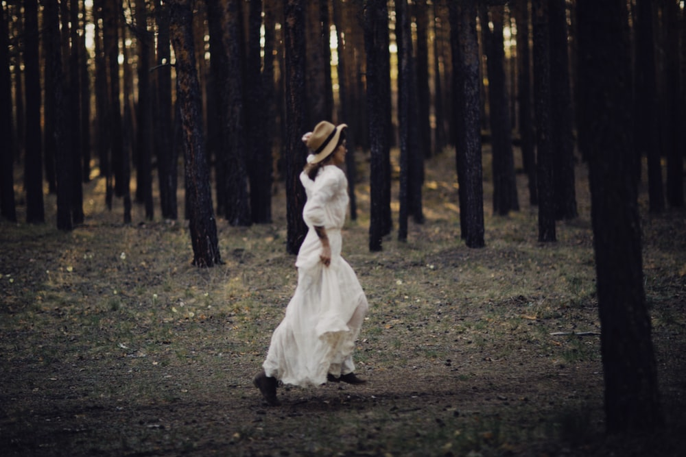 woman in white dress walking on forest during daytime