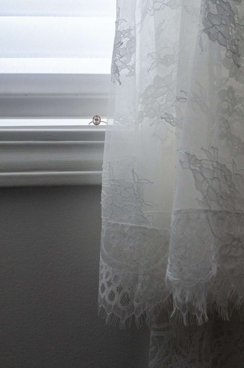 white floral window curtain near white window blinds