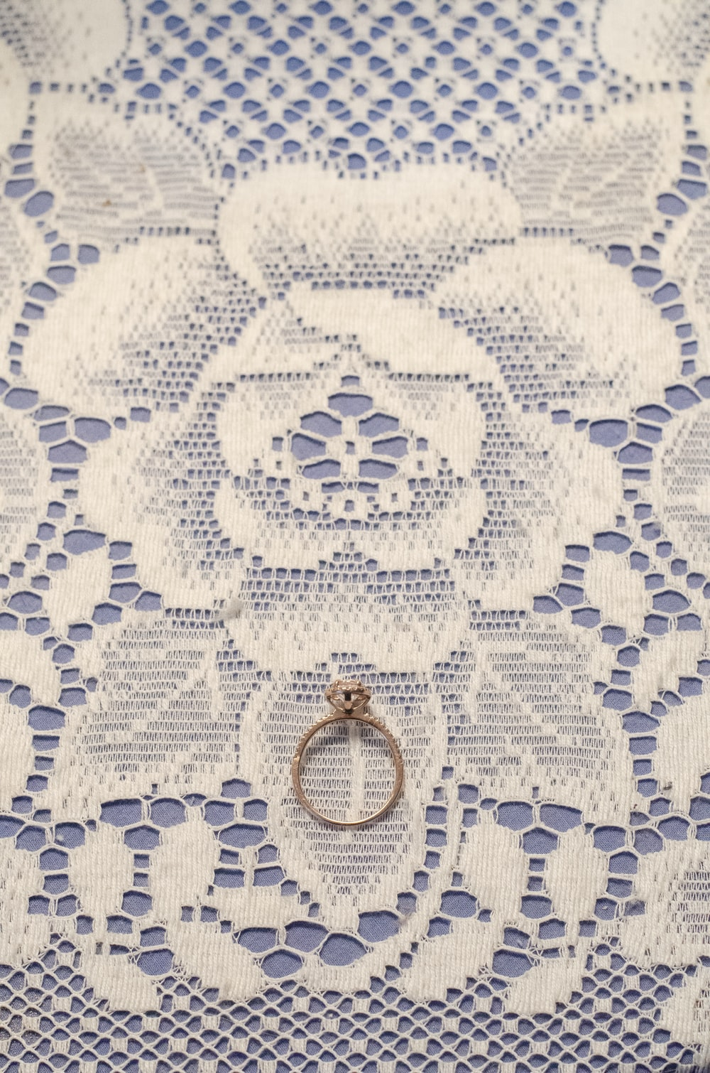 gold ring on white and blue floral textile