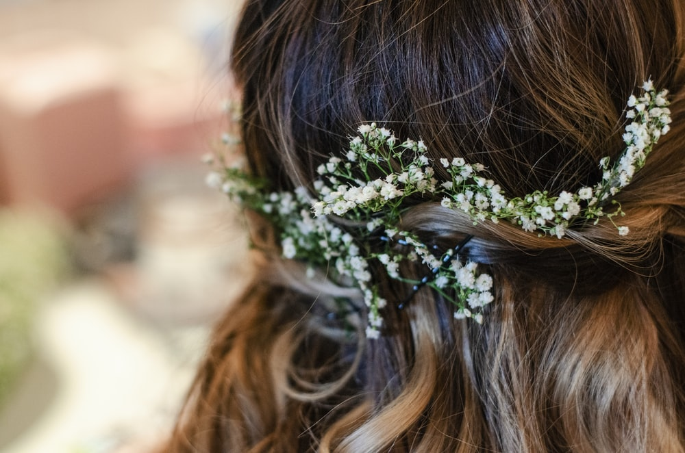 woman with brown hair wearing white flower headband