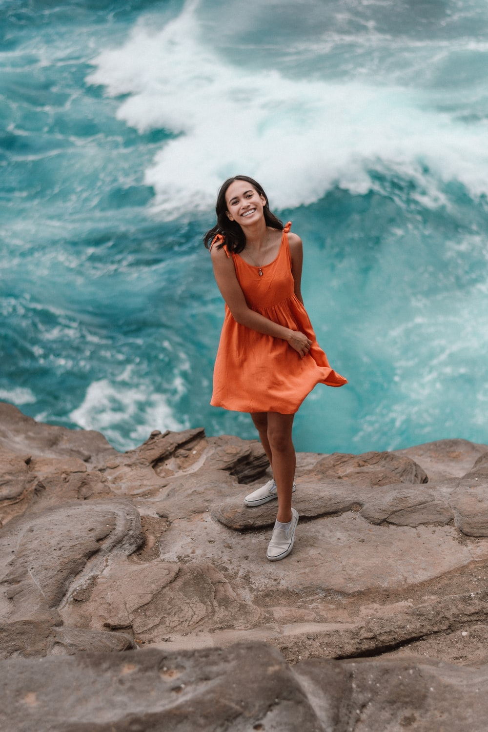 woman in orange sleeveless dress standing on rock formation near body of water during daytime