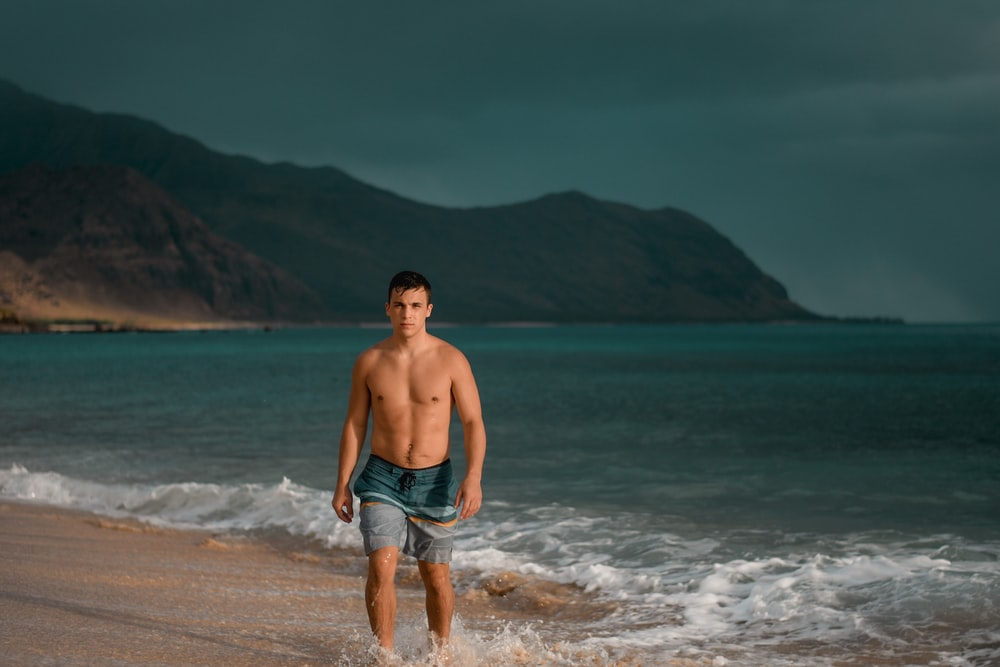 topless man in blue denim shorts standing on seashore during daytime