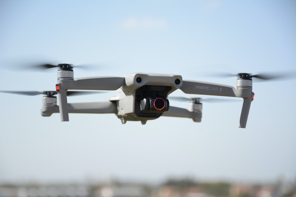 white and black drone in mid air during daytime
