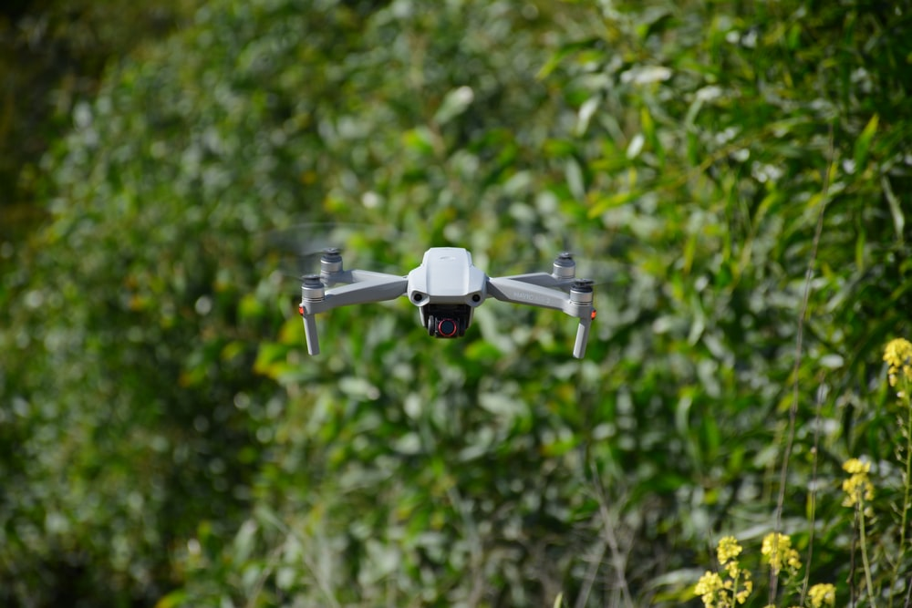 white drone flying during daytime