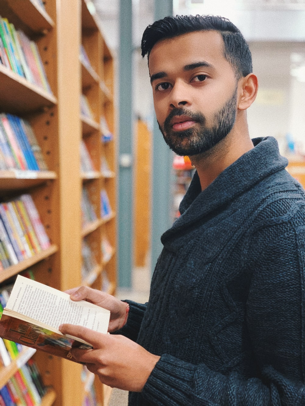 man in black sweater reading book