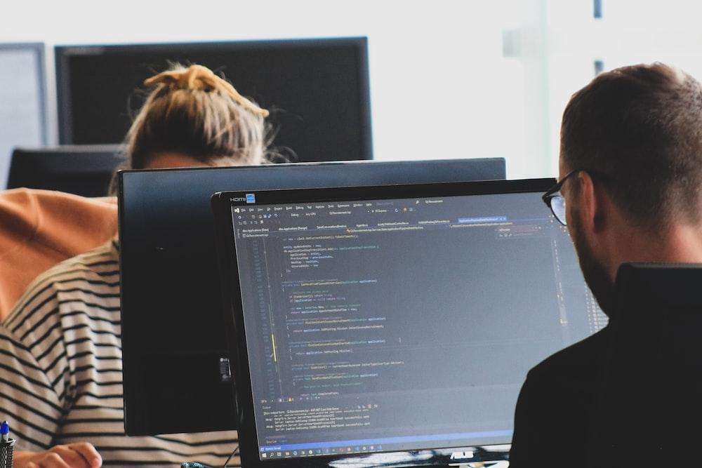 woman in black shirt sitting beside black flat screen computer monitor