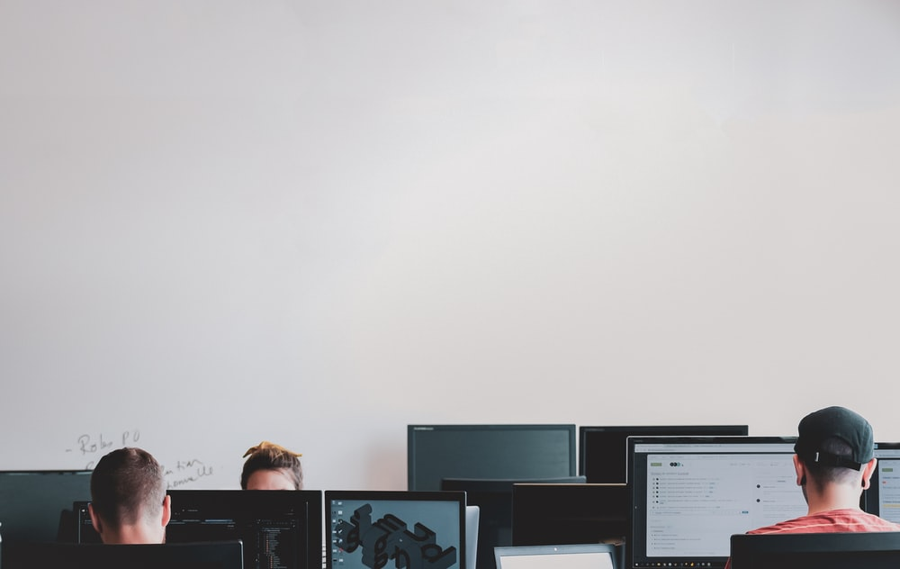 man in black jacket sitting beside black flat screen computer monitor