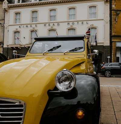 yellow and black vintage car parked beside white concrete building during daytime
