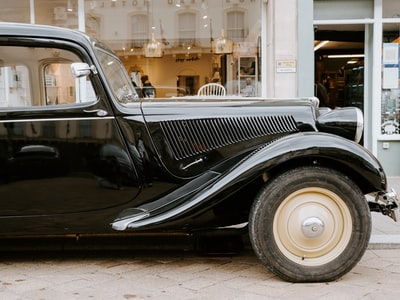 black classic car parked on sidewalk during daytime