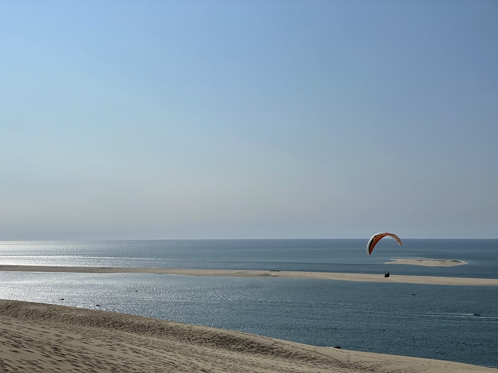 person in orange and yellow parachute over the sea during daytime