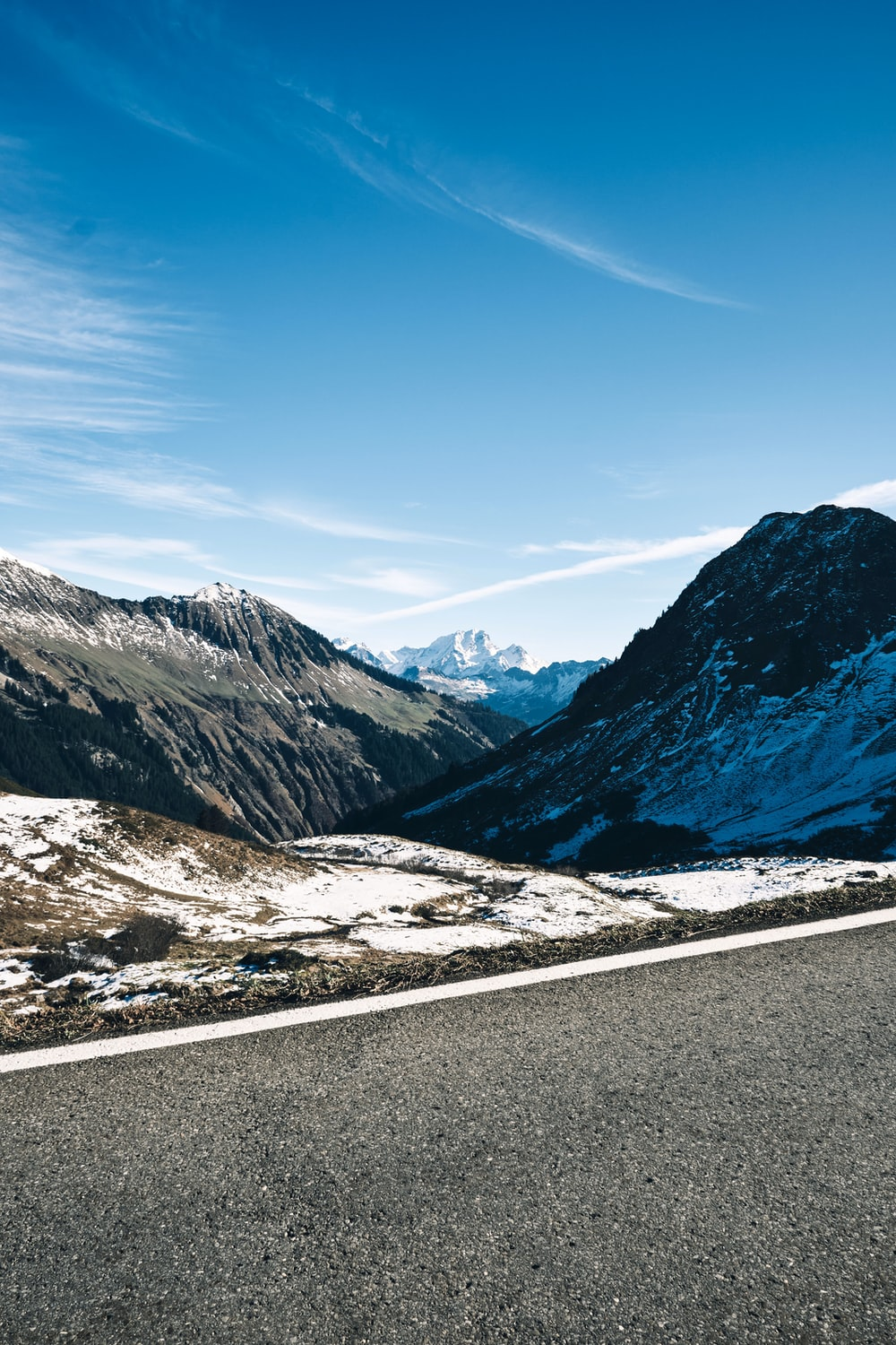 gray concrete road near snow covered mountains under blue sky during daytime