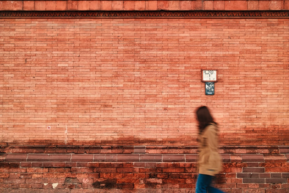 woman in gray hoodie and blue denim jeans walking on brown brick wall
