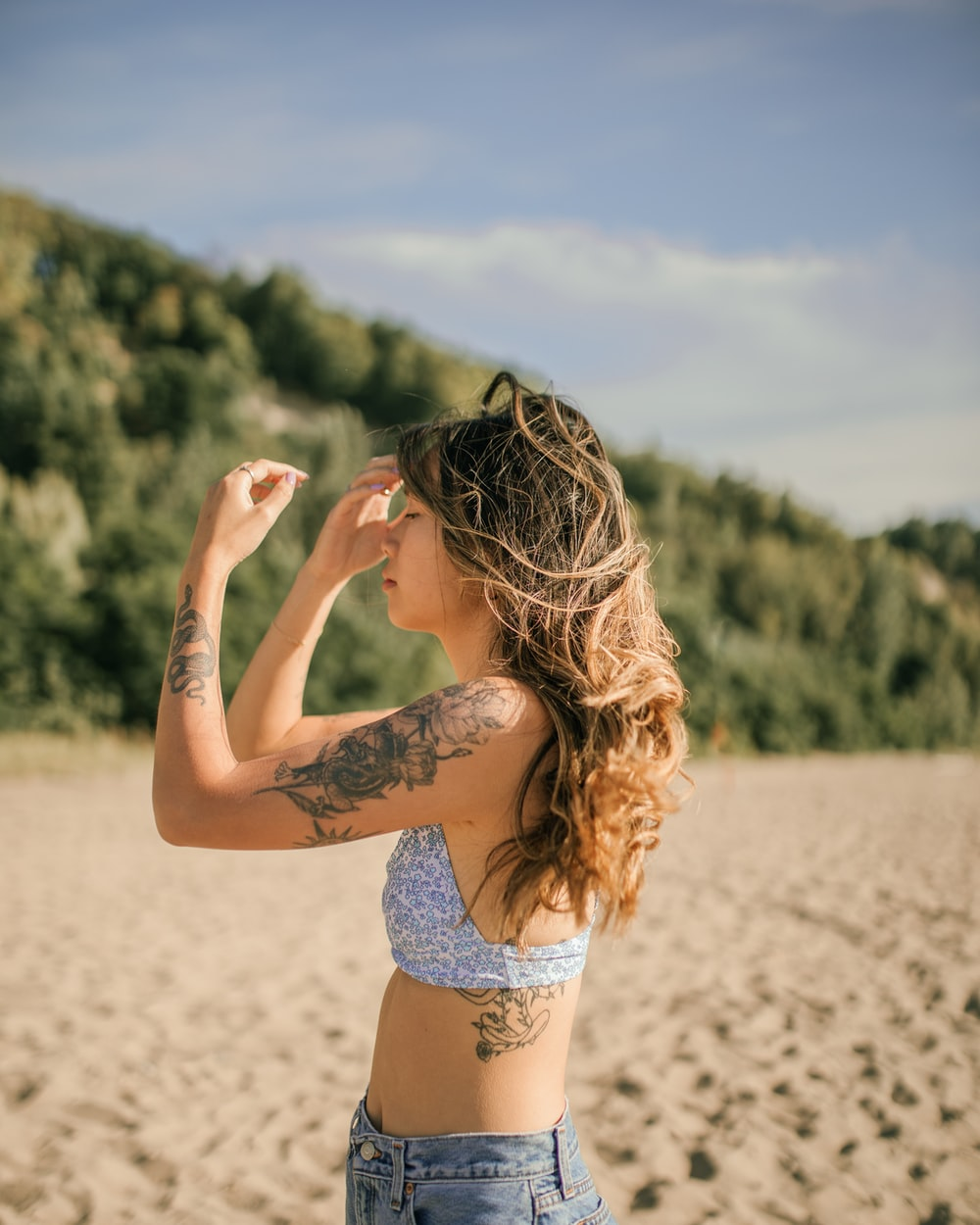 woman in blue and white floral bikini standing on brown sand during daytime