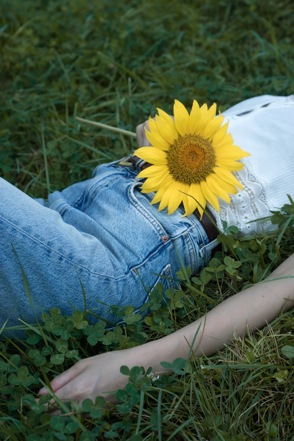 person in blue denim jeans sitting on white textile with yellow sunflower on her lap