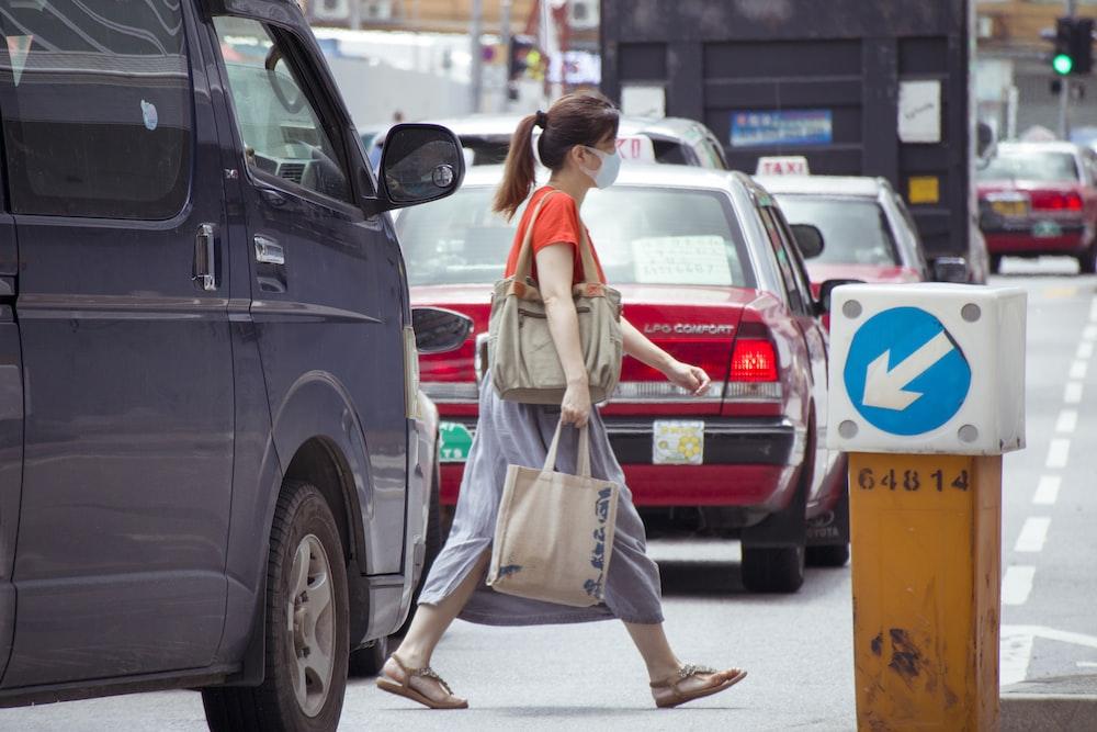 woman in white dress holding white plastic bag standing beside black car during daytime
