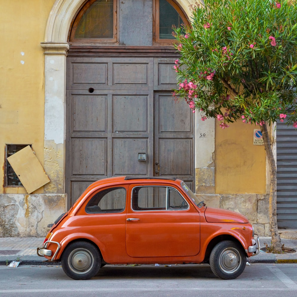 red volkswagen beetle parked beside brown concrete building during daytime