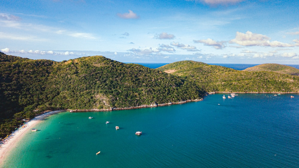 aerial view of boats on sea near green mountain under blue sky during daytime