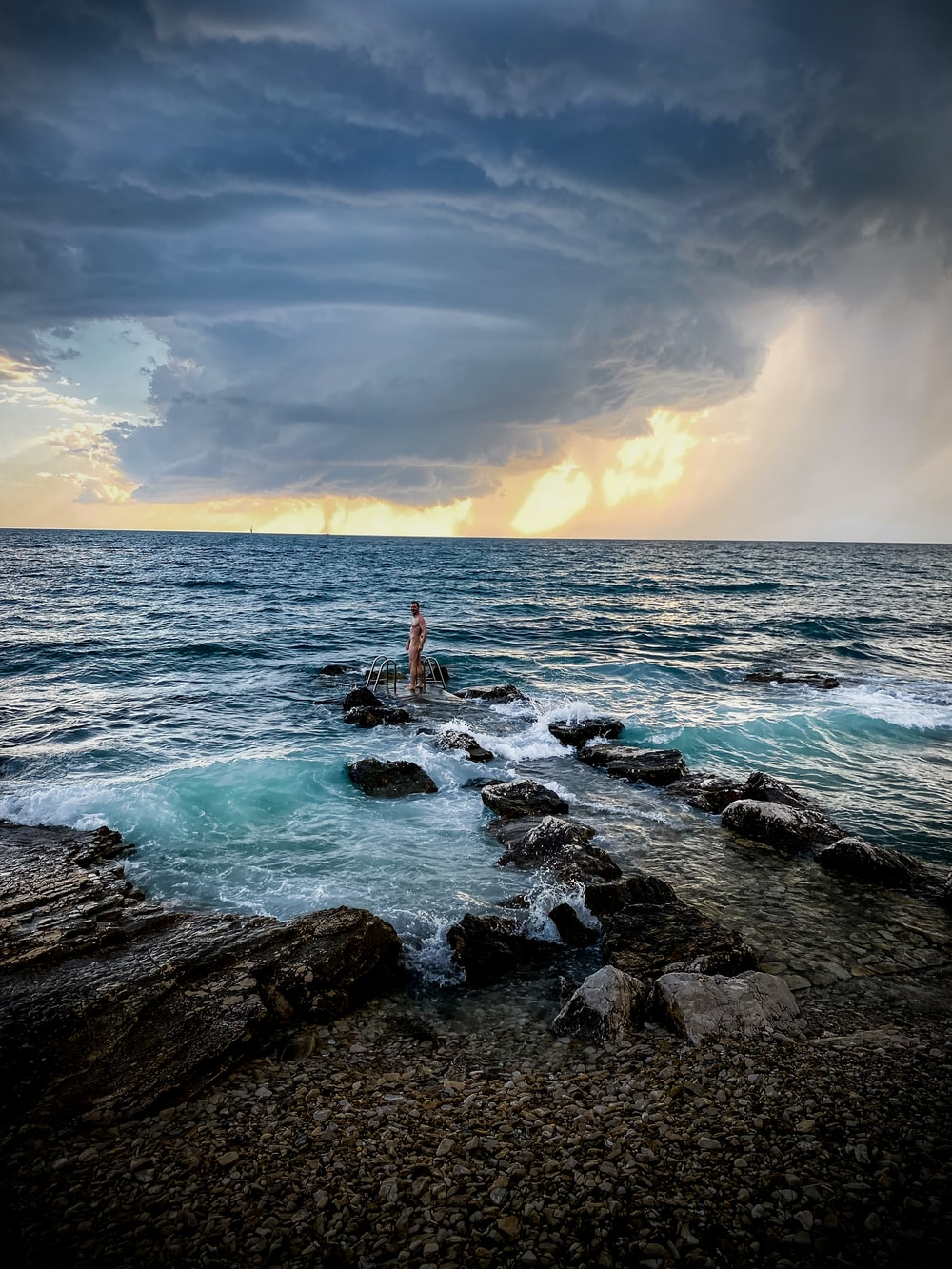 person standing on rock formation in sea during daytime