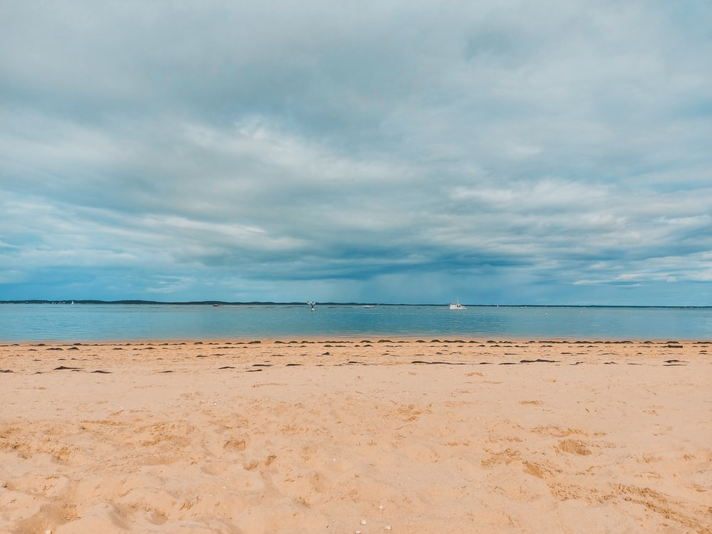 brown sand near body of water under white clouds during daytime