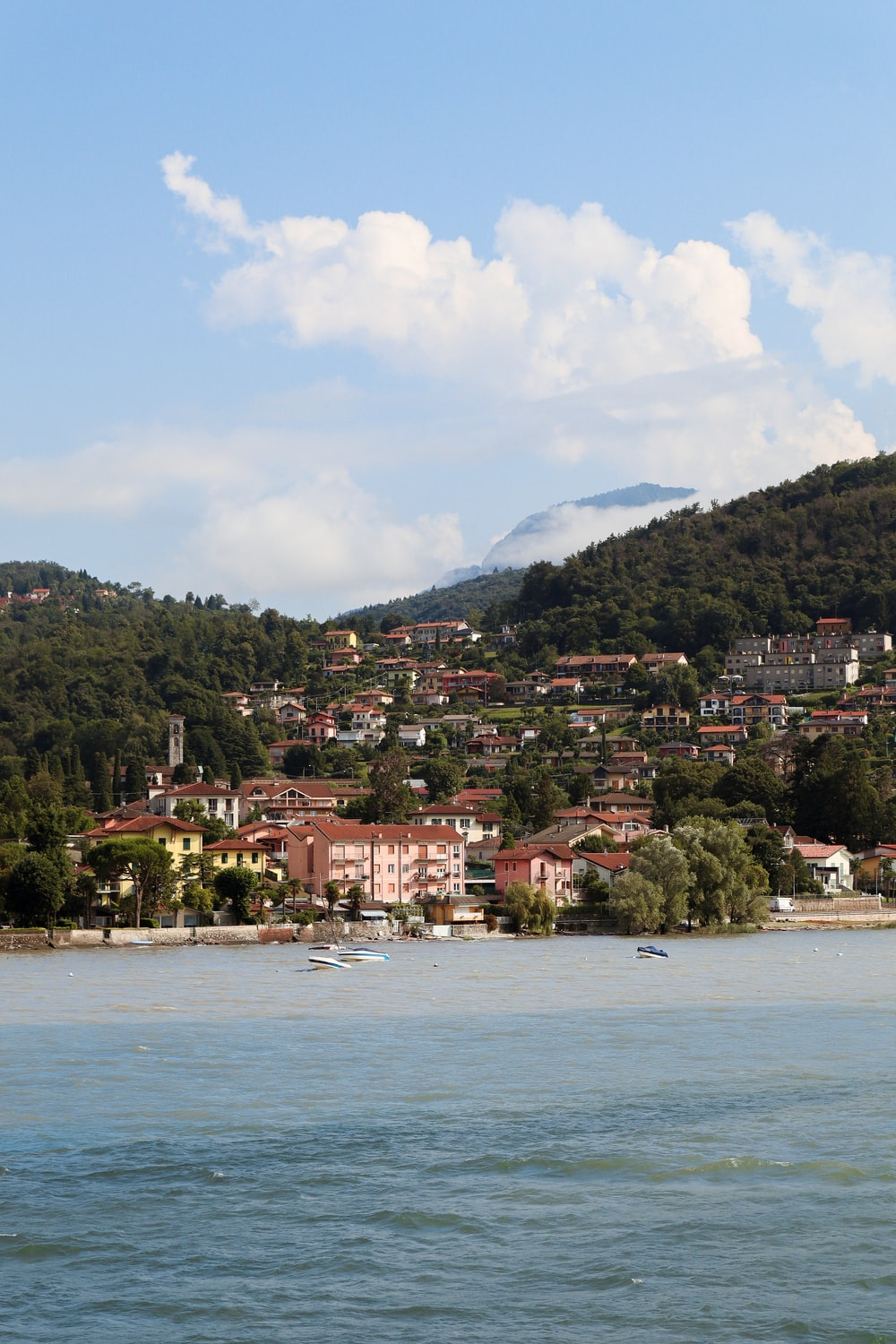 houses on mountain near body of water during daytime