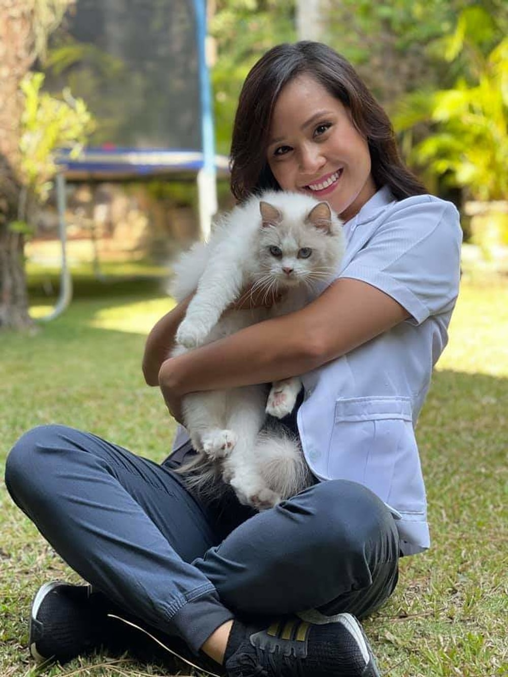 woman in blue polo shirt holding white long fur cat