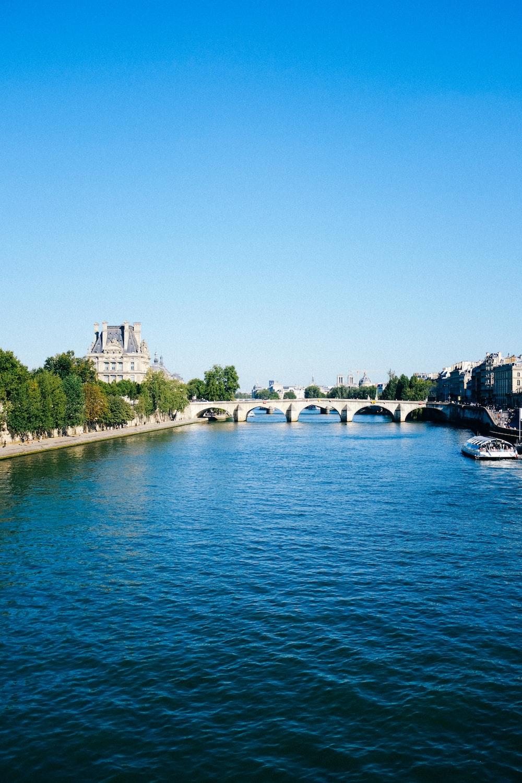 white boat on river near bridge during daytime