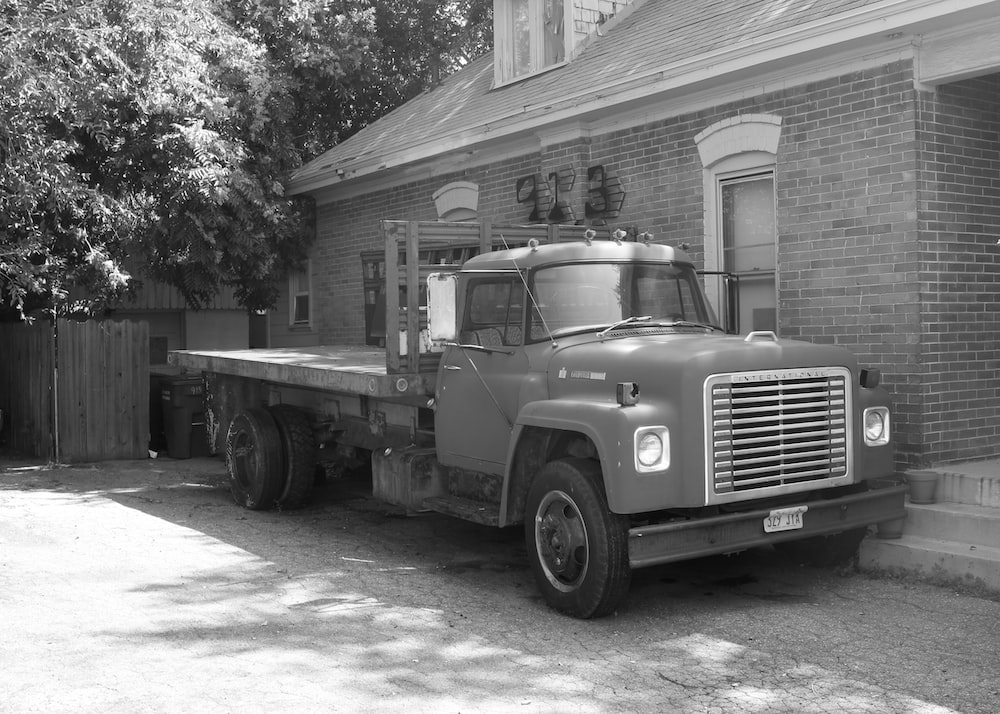 grayscale photo of truck in front of wooden house