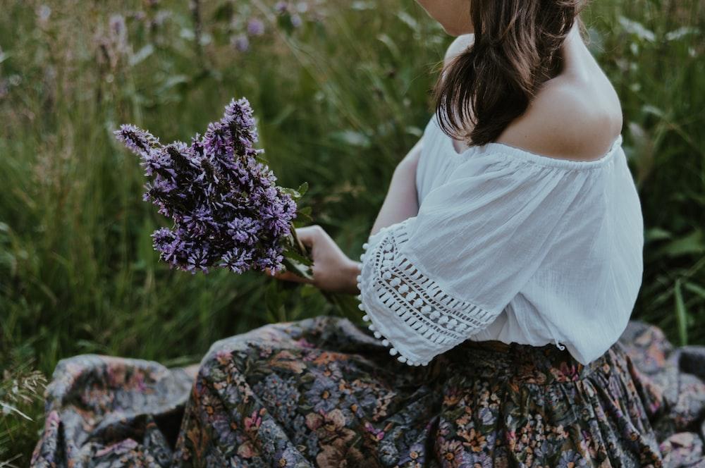 woman in white dress holding purple flowers