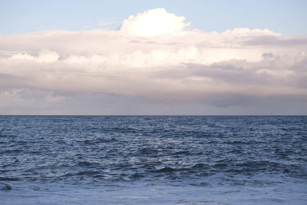 blue sea under white clouds during daytime