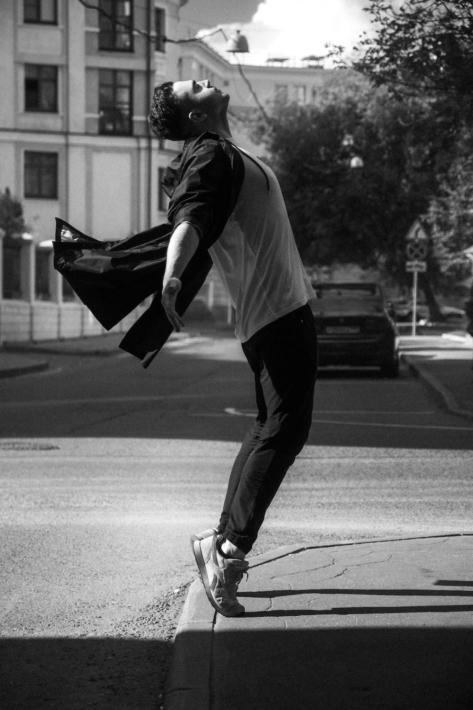 man in white shirt and black pants walking on street
