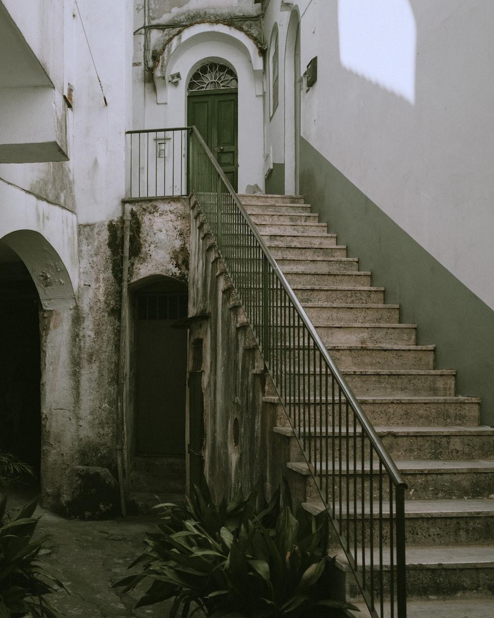 black metal staircase near white concrete building