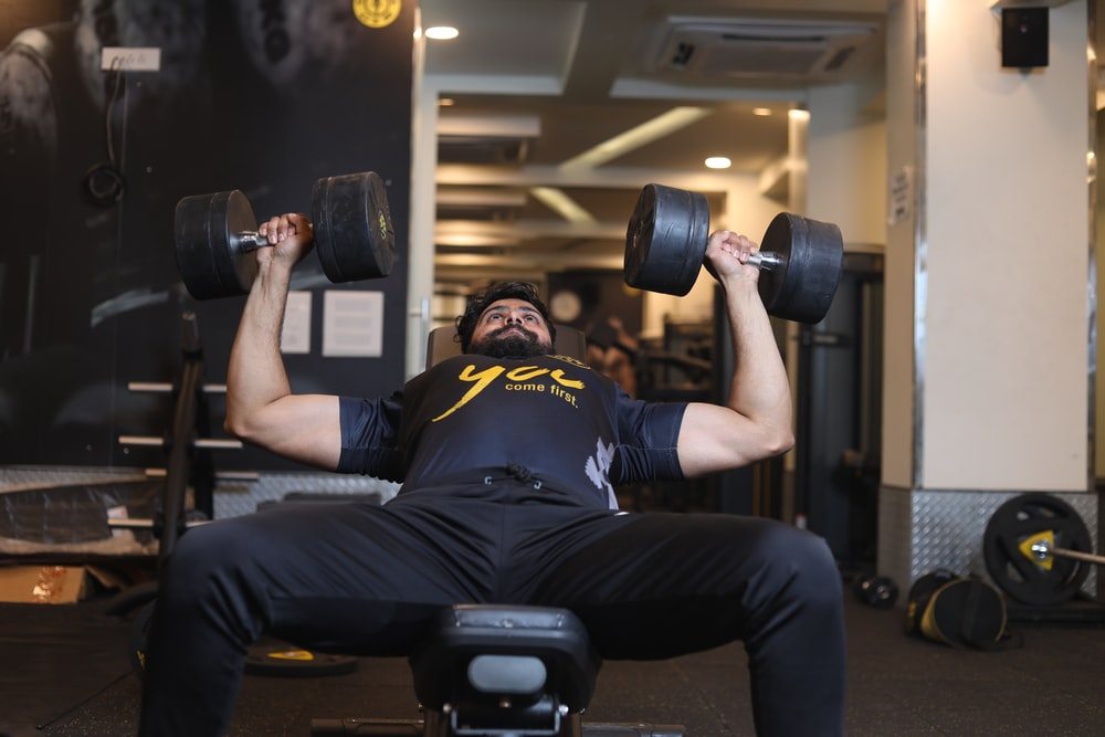 man in black and yellow adidas jersey shirt and black pants sitting on black exercise bench
