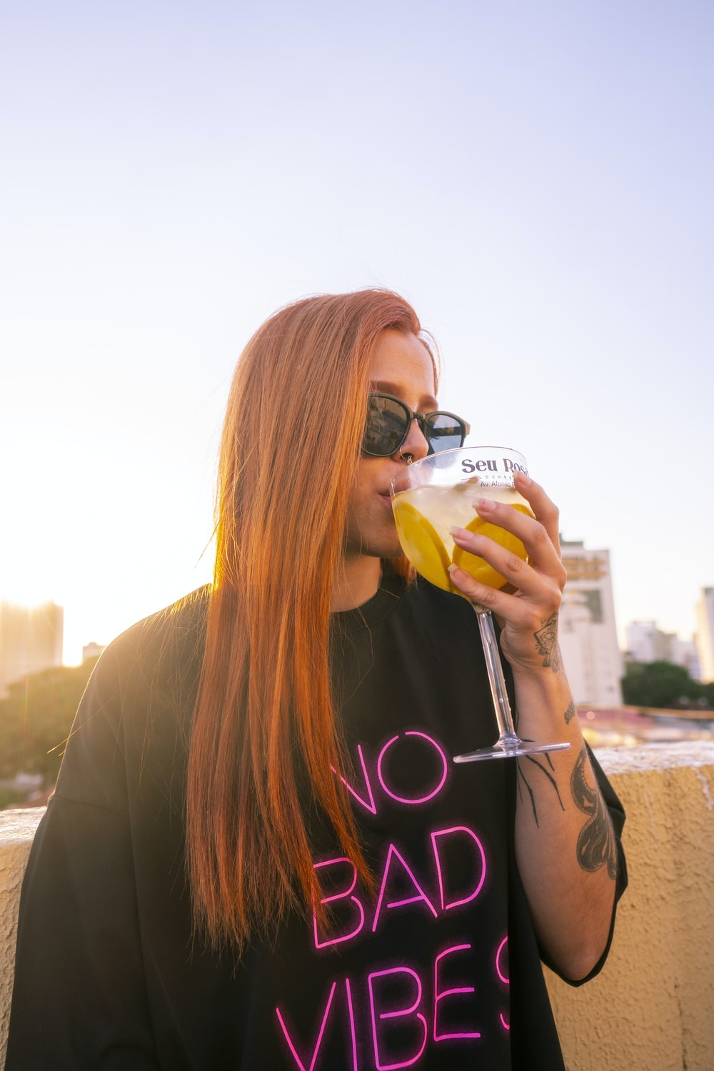 woman in black long sleeve shirt drinking from clear drinking glass during daytime