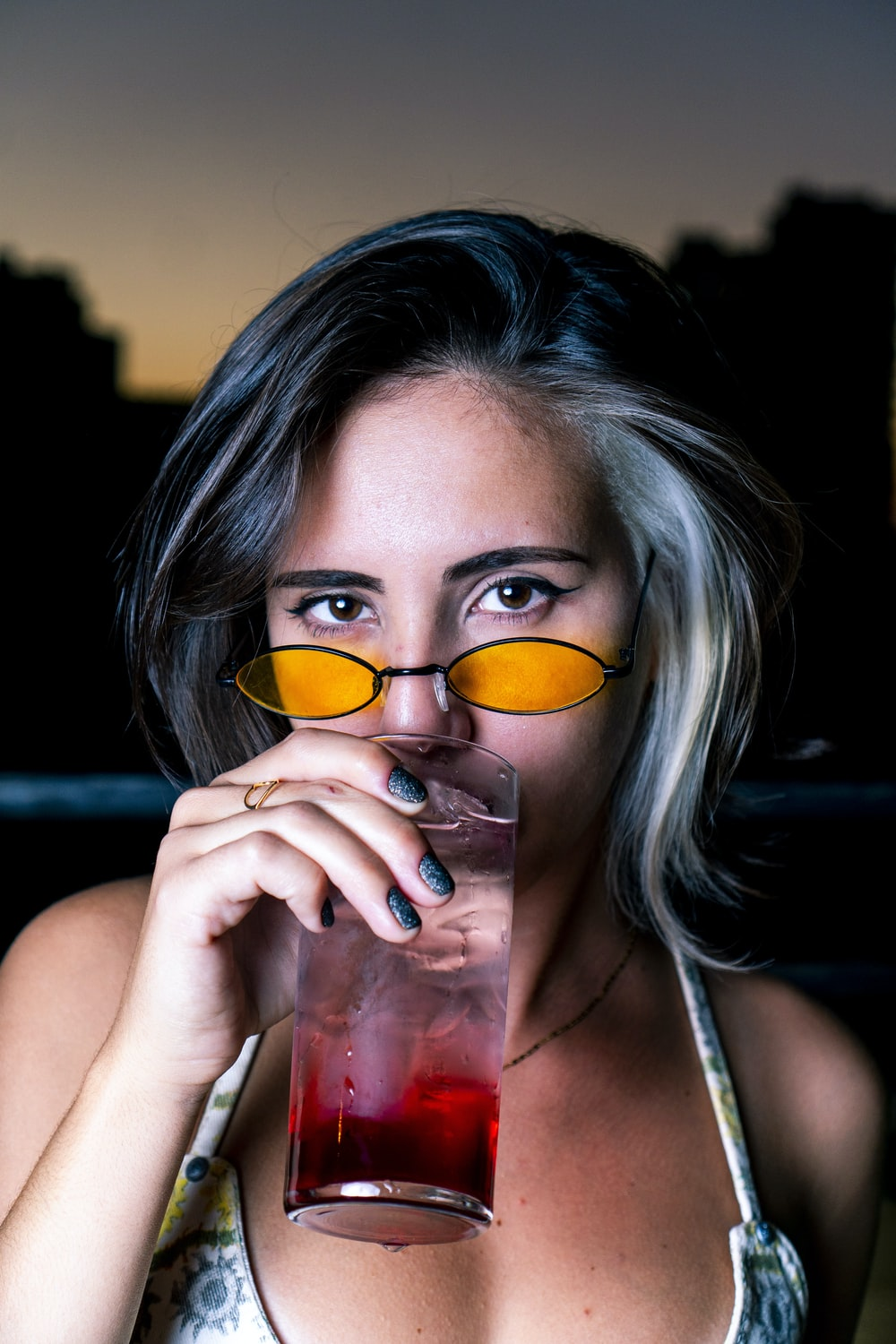 woman in white tank top holding clear drinking glass