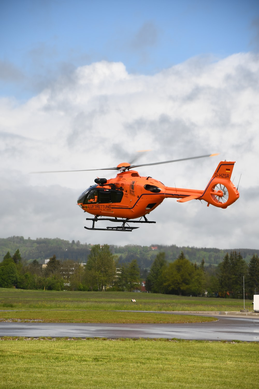 orange helicopter flying over green trees during daytime