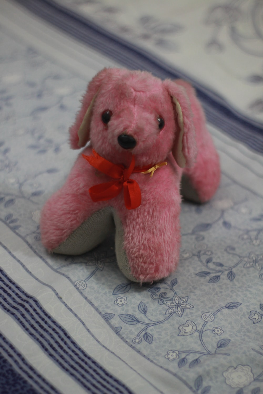 pink bear plush toy on white and blue textile