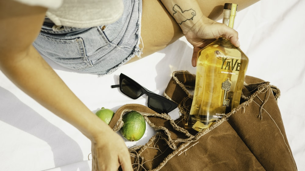 woman in blue denim shorts holding clear glass bottle with yellow liquid