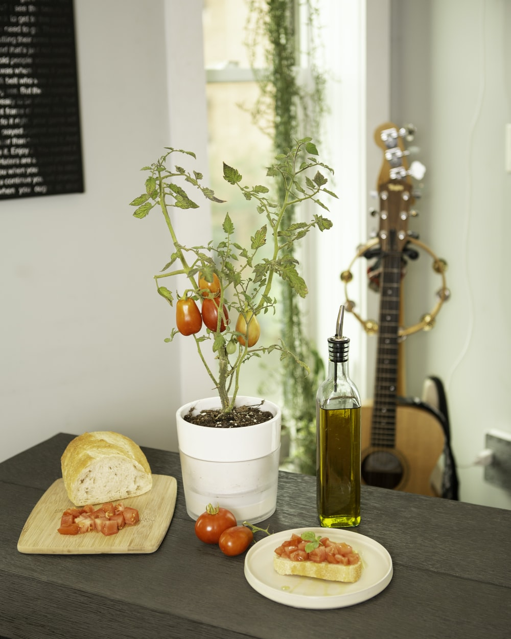 red berries on white ceramic bowl beside brown wooden acoustic guitar