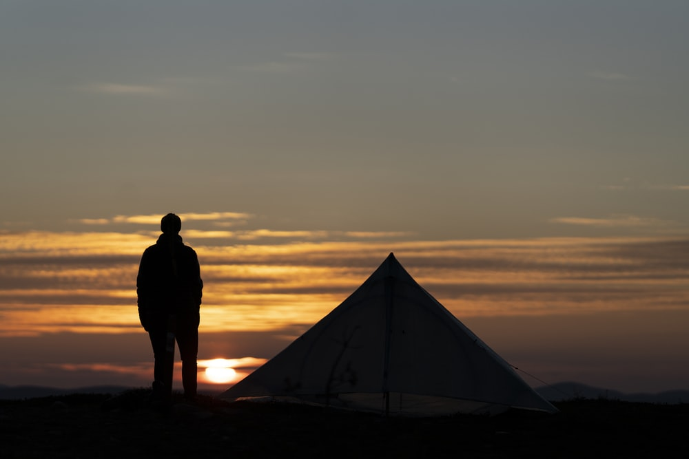 silhouette of man standing near tent during sunset