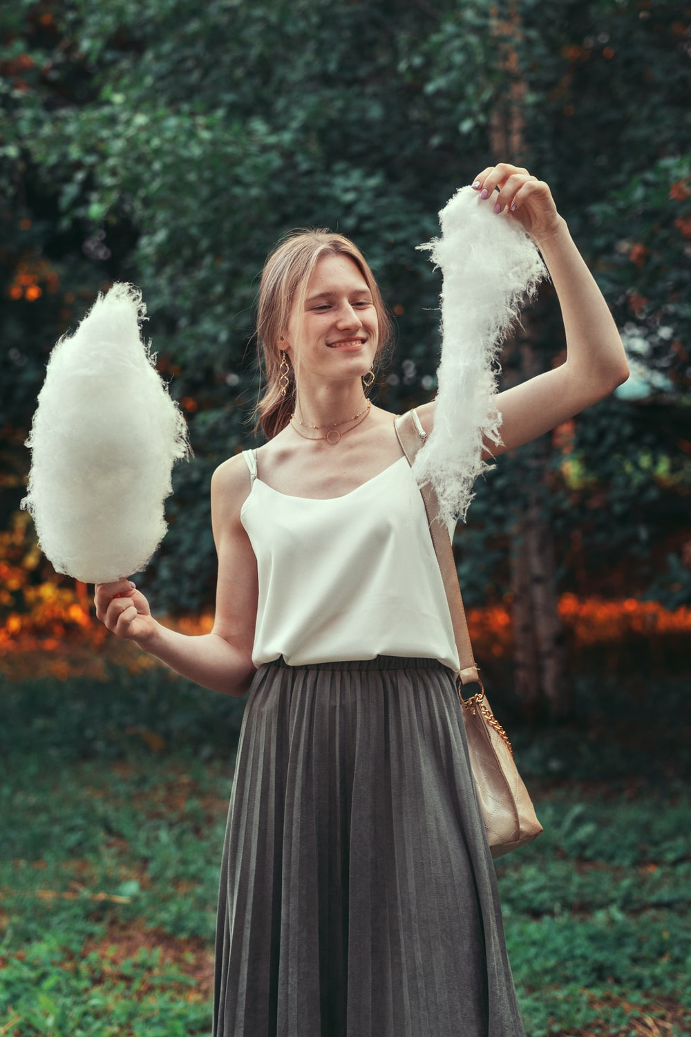 woman in white tank top and black skirt holding white cotton candy