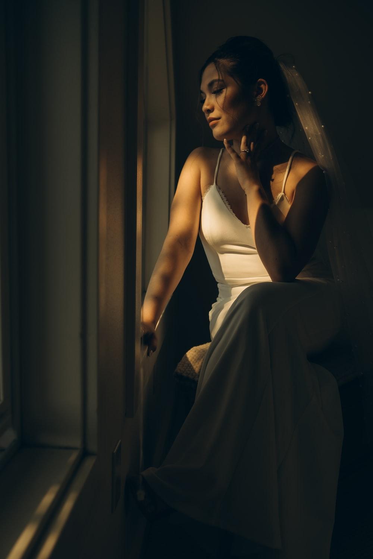 woman in white spaghetti strap dress sitting on chair