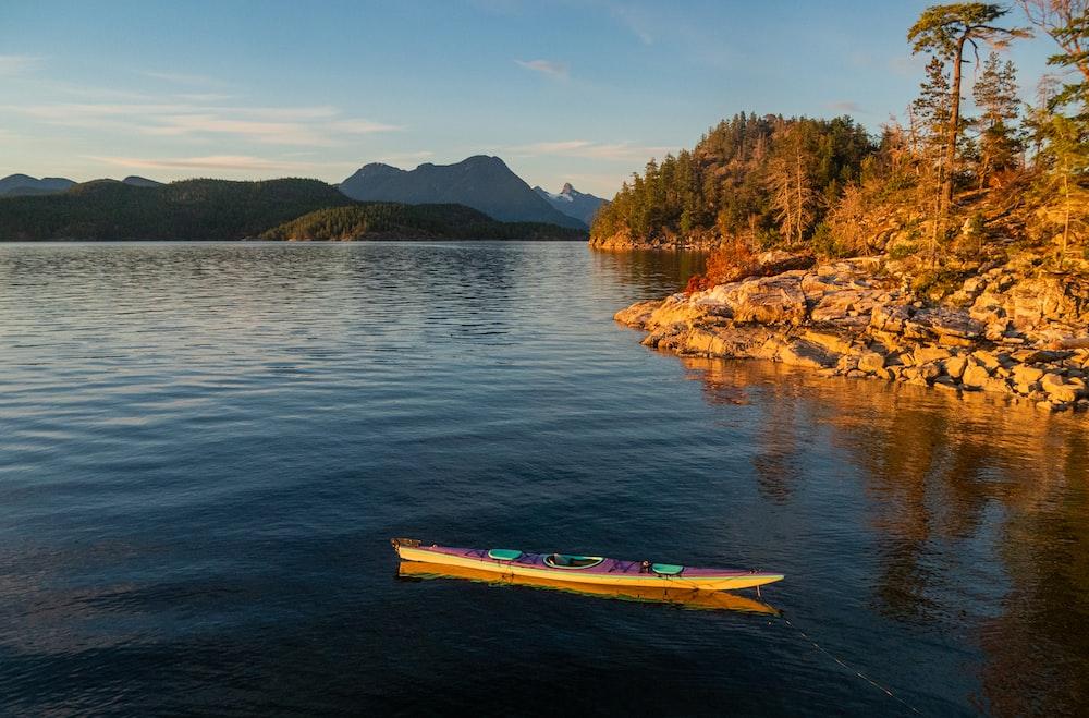 yellow kayak on blue sea near brown rock formation during daytime