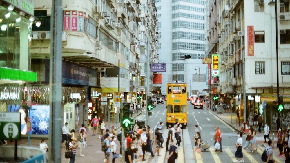 people walking on street near yellow bus during daytime
