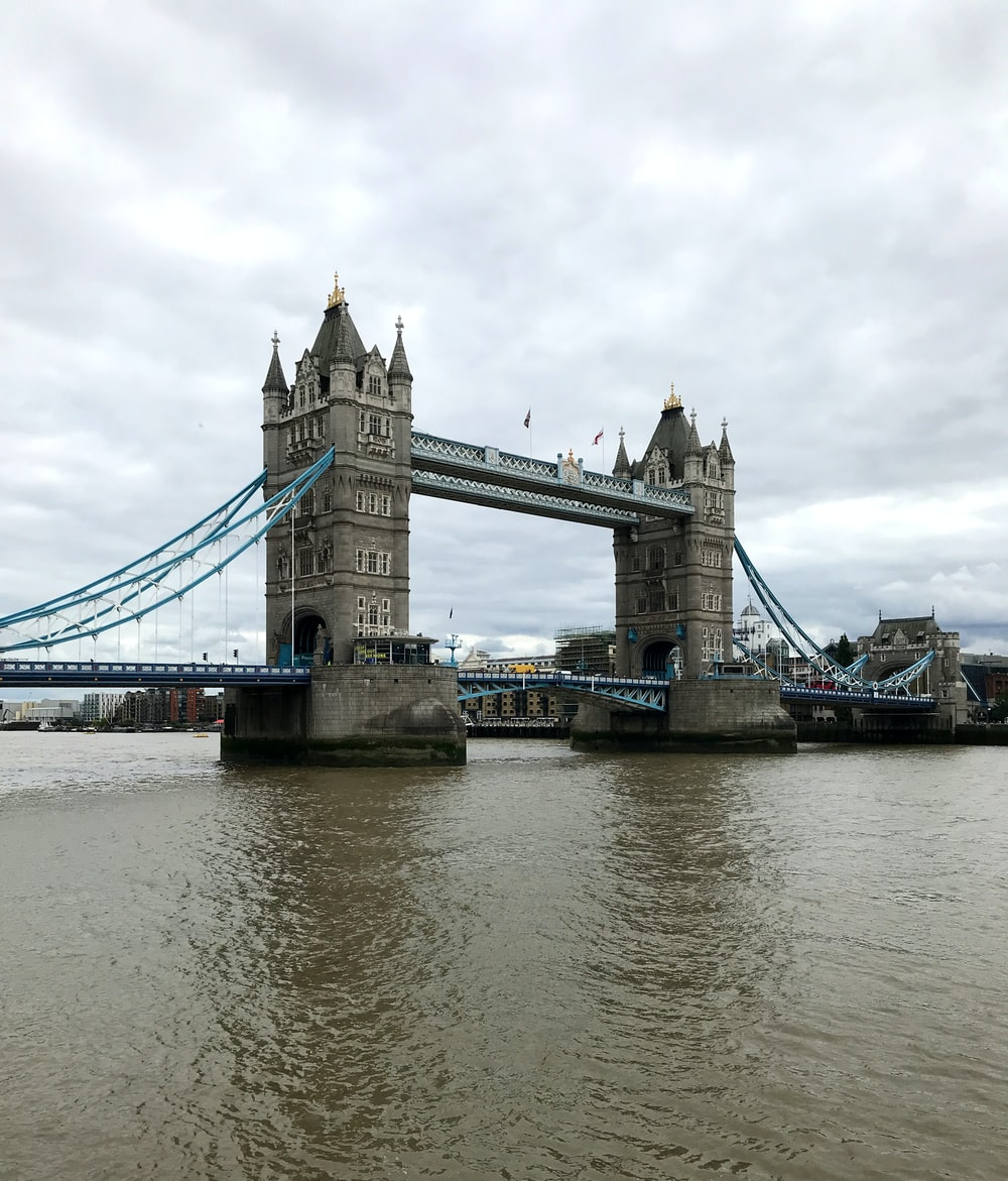 gray concrete bridge over river under cloudy sky during daytime