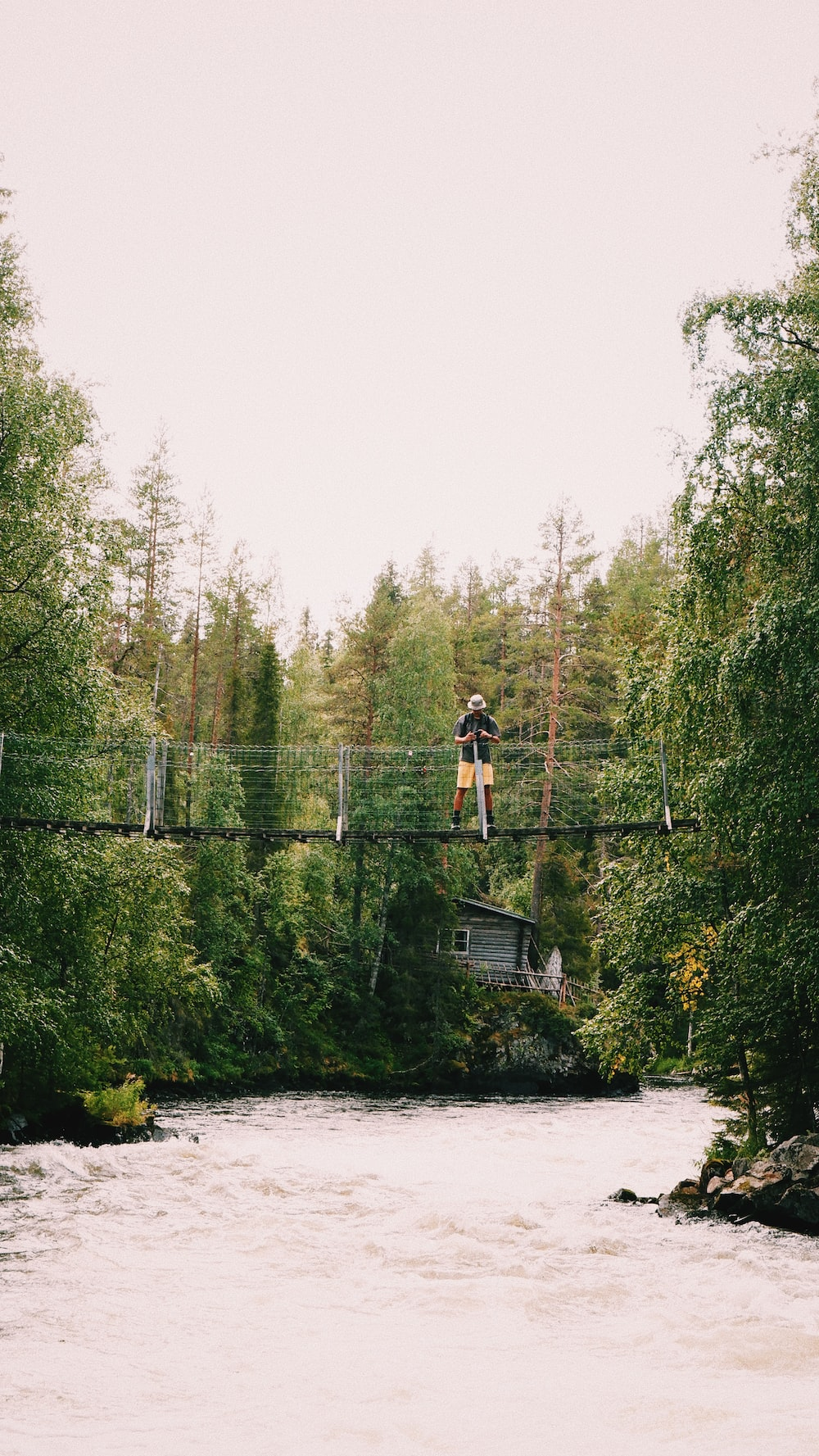 man in black t-shirt and black shorts standing on bridge over river during daytime