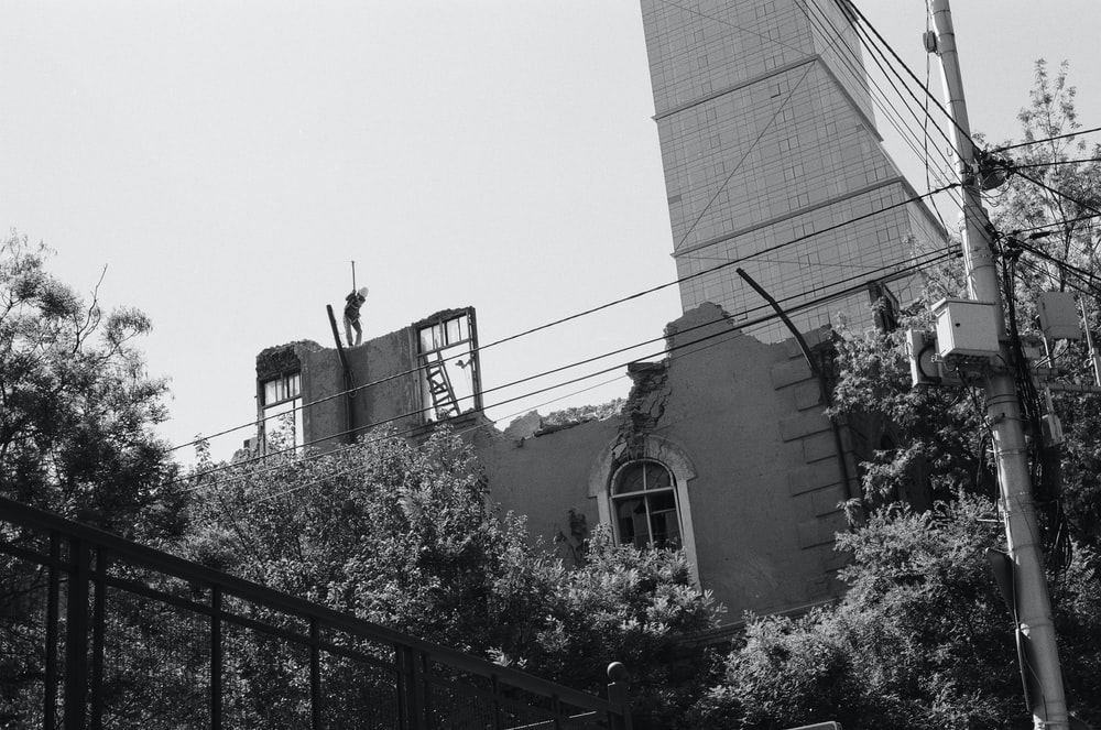 grayscale photo of building near trees