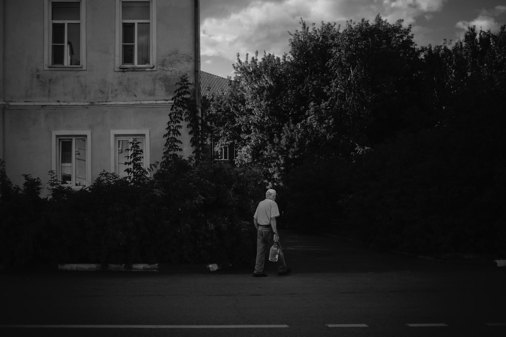 grayscale photo of man in white shirt and pants standing on road