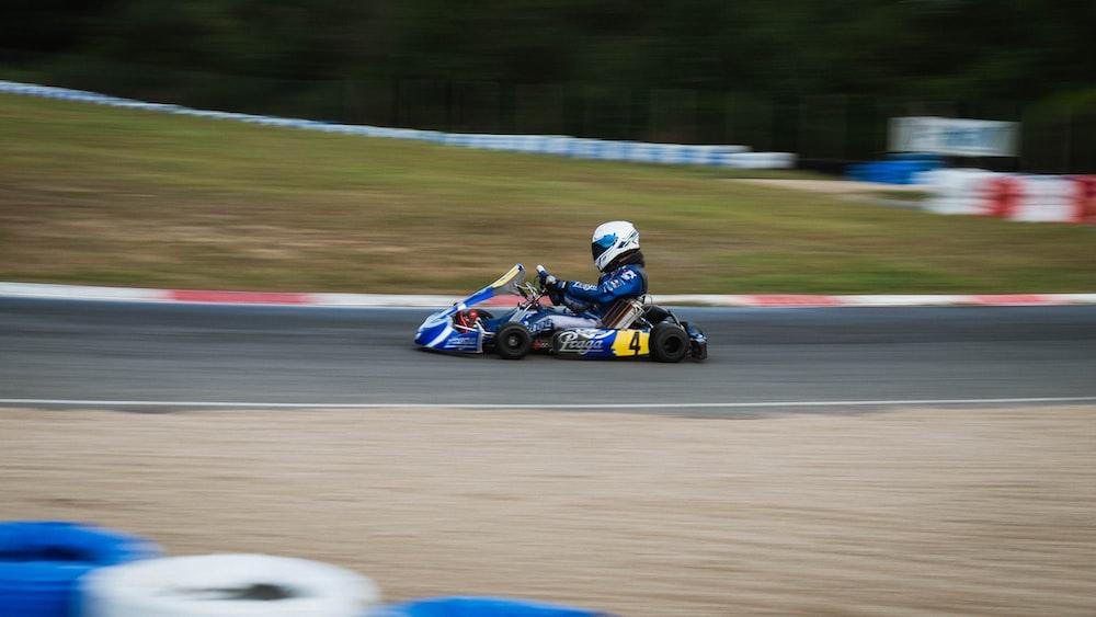 man riding on blue and black go kart
